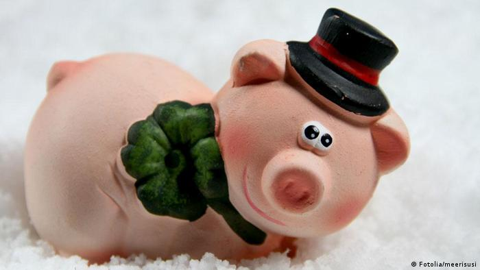 Decorative piglet figurine with a hat and a tie and a four-leaf clover (Fotolia/meerisusi)