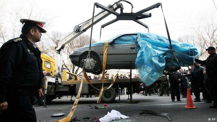 In this photo provided by the semi-official Fars News Agency, people gather around a car as it is removed by a mobile crane in Tehran, Iran, Wednesday, Jan. 11, 2012. Two assailants on a motorcycle attached magnetic bombs to the car of an Iranian university professor working at a key nuclear facility, killing him and wounding two people on Wednesday, a semiofficial news agency reported. (Foto:Fars News Agency, Mehdi Marizad/AP/dapd)