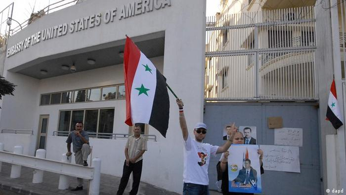 FILE - In this Friday, July 8, 2011 file photo, a pro-Syrian President Bashar Assad protester, hold Assad's portrait and wave their country flag as they protest against the visit of the US Ambassador to Syria Robert Ford to the Syrian city of Hama, in front the US embassy in Damascus, Syria. The U.S. has pulled its ambassador out of Syria over security concerns, blaming President Bashar Assad's government for the threats. State Department spokesman Mark Toner said Monday Oct. 24, 2011 that Ambassador Robert Ford returned to Washington this weekend after credible threats against his personal safety.(Foto:Muzaffar Salman, File/AP/dapd)
