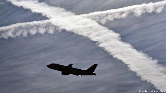 Ein Flugzeug startet vor dem Hintergrund von zwei Kondensstreifen am Himmel