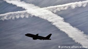 An airplane takes off amid vapor trails Photo: Frank Rumpenhorst dpa/lhe