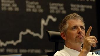 A stock trader sits in front of a display board (ddp images/AP Photo/Bernd Kammerer)