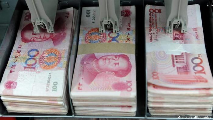 A bank teller counts renminbi bank notes in Shenyang, EPA/MARK