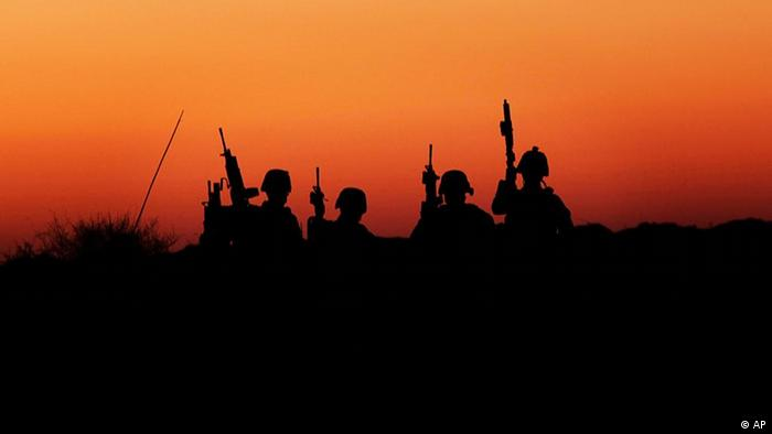 United States Marines from the 2nd MEB, 4th Light Armored Reconnaissance Battalion gather during a patrol where a gun battle with insurgents occurred earlier, near Shabu in the volatile province of Helmand, southern Afghanistan, Saturday, Dec. 5, 2009. (AP Photo/Kevin Frayer)