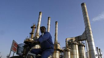 A man on a bicycle outside an Iranian oil refinery