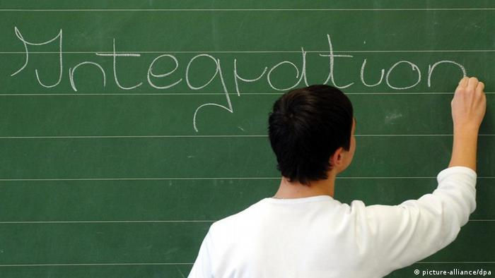 A student neatly writes the word 'integration' on a chalk board