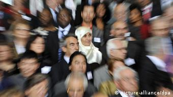 A crowd of people of various ethnicities stands together Photo: Rainer Jensen dpa/lbn