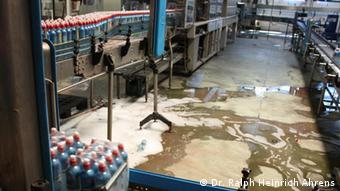 Bottles on the bottling line with foamy water on the ground
