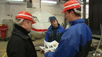 Three employees looking at paperwork in front of a high-speed train