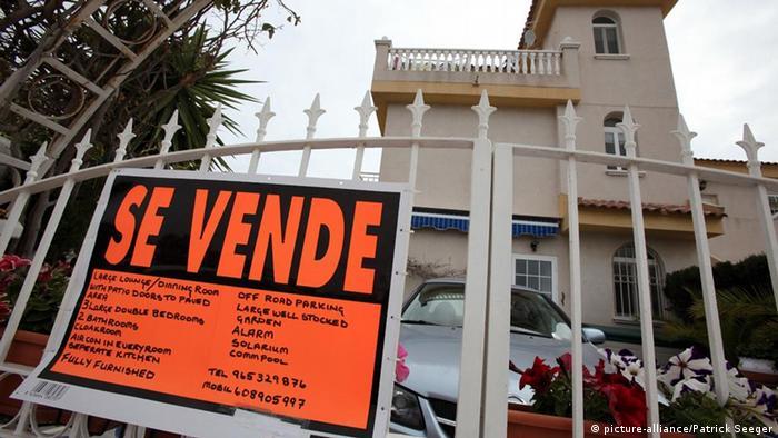 Вилла. на заборе перед которой вывешена информация о ее продаже