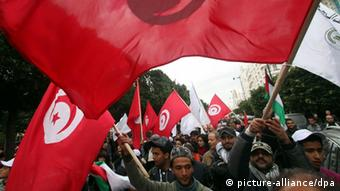 Tunisians wave their national flag as they gather to mark the anniversary EPA/STRINGER