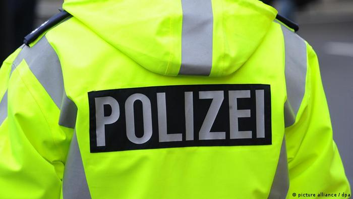 A German policeman wearing a high-visibility jacket stands with his back to camera, with German word Polizei clearly visible
