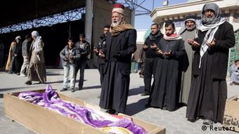 Residents pray near the coffin of a victim who was killed in the bomb attack