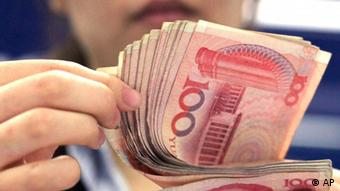 A bank clerk counts Chinese 100 Yuan notes in Shanghai.