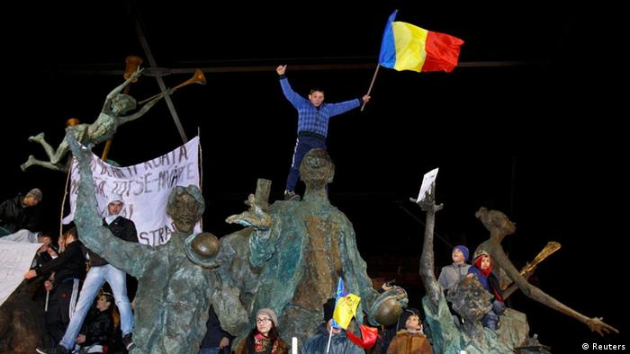 A protester waves a flag and shouts slogans from the top of a statue the University Square in Bucharest, January 15, 2012. Thousands of Romanians gathered on Sunday in capital Bucharest and large cities across the country for a fourth consecutive day of protests that started out against a controversial healthcare reform bill and widened to government austerity measures. REUTERS/Bogdan Cristel (ROMANIA - Tags: BUSINESS POLITICS CIVIL UNREST)