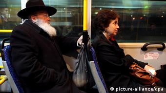 An ultra-Orthodox man sits behind a woman on a bus