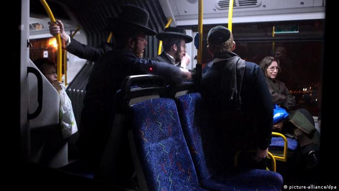 ultra-Orthodox men look on as a woman sits at front of bus
