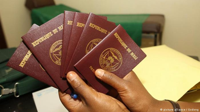 Two hands holding several Malian passports