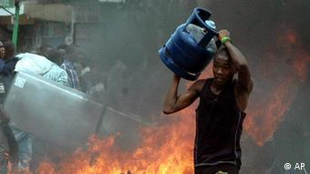 A man runs across the road holding a looted gas cylinder from a shop Monday, Dec. 31, 2007, at the Bamburi estate along the Old Mombasa-Malindi road, in Kenyas coastal town of Mombasa, during looting in protest against the announcement of President Mwai Kibaki of the Party of National Unity as the winner of the December 27th elections against Raila Odinga of Orange Democratic Movement.(AP Photo)