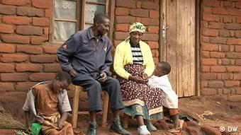Picture of a Malawian family outside their mud house.