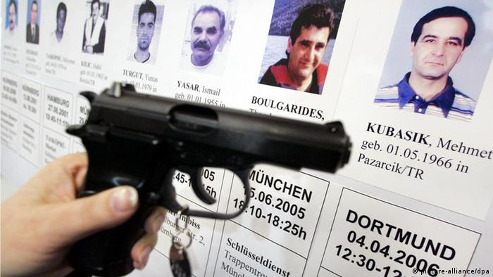 A hand holds a gun in front of a newspaper showing victims' faces and names (picture-alliance/dpa)