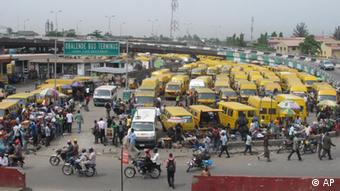 People throng around the Obalende Bus Terminus, where market stall holders try to sell good to the traveling public, in Lagos, Nigeria
