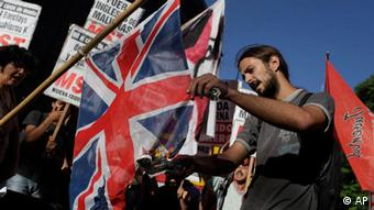 A man burns a British flag in front of the Foreign Ministry building in Buenos Aires