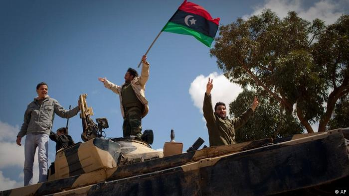 Libyan rebels celebrate on a captured tank in the outskirts of Benghazi