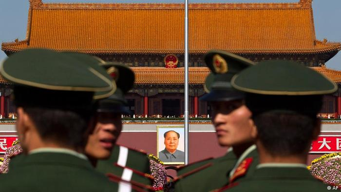 Paramilitary policemen look back while patrolling on the Tiananmen Sqaure in front of the late communist leader Mao Zedong's portrait in Beijing, China,