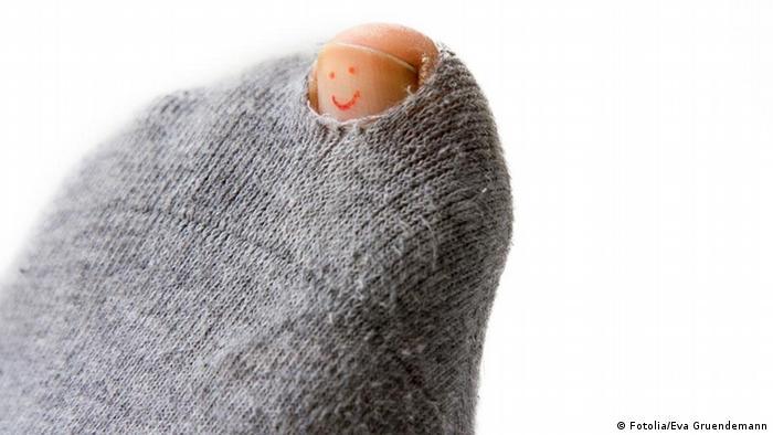 Durch das Loch einer Socke ist ein großer Zeh zu sehen, auf den ein Smiley gemalt ist