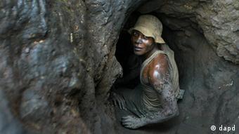 Ein Mann zwängt sich in den Eingang einer Mine (Foto: AP)