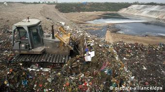 A bulldozer pushes trash into the Chongming landfill near Shanghai, China