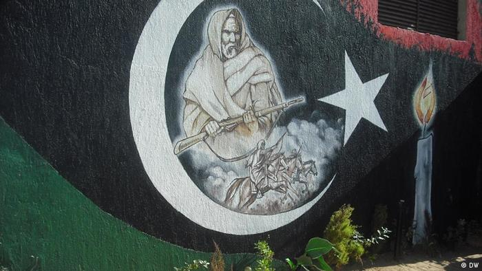 Graffiti in Libya. Man holding weapon painted into crescent on Libyan revolutionary flag.