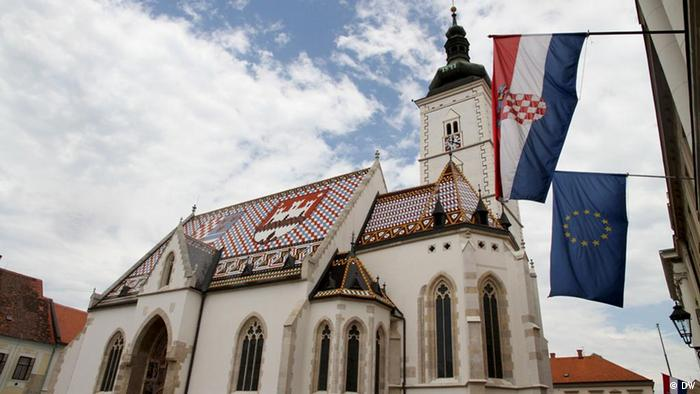 Titel: Zagreb, Kroatien Beschreibung: Saint Mark's Church, Zagreb, Croatia. The flag of the European Union hangs beside the Croatian flag from the entrance of the Croatian Parliament, prepared for the country's accession to the EU in 2013. The EU flag faces Saint Mark's Church, a juxtaposition of Croatia's past and future. Schlagworte: Zagreb, Stadt, Zentrum, Kroatien, Crkva svetog Marka, EU, Parlament Autor: Christopher Bobyn Datim: January 2012
