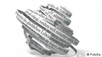 Symbolbild: ein gedrehtes Knäuel eines langen Papierbandes mit vielen Wörtern