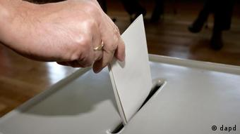 A person votes (close-up of hand with ballot)