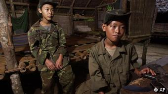 ** TO GO WITH STORY SLUGGED: MYANMAR CHILD SOLDIERS BY GRANT PECK ** Two young ethnic Karen boys look on following ceremonies to honor those killed in fighting with the Myanmar government Aug. 12, 2001, at Kaw Thoo Lei, Myanmar. Myanmar's military government, already under criticism for abuses, is recruiting children as young as 10 into its armed forces, a U.S. rights group charged in a report released Wednesday, Oct. 31, 2007. (AP Photo/David Longstreath) ***Zu Glass, Birmas Mönche - Schwierige Menschenrechtslage auch in Myanmar***