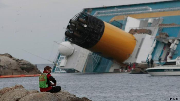 A rescuer sits on a rock near the cruise ship Costa Concordia keeled over on its side in the tiny Tuscan island of Giglio, Italy, Thursday, Jan. 19, 2012. The $450 million Costa Concordia was carrying more than 4,200 passengers and crew when it slammed into well-charted rocks off the Tuscan island of Giglio. Eleven people have been confirmed dead and 21 others are still missing. (Foto:Gregorio Borgia/AP/dapd)
