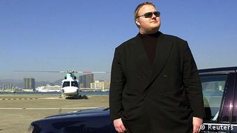 Kim Schmitz posiert in schwarzem Anzug vor Luxuswagen und Businessjet (Foto: Reuters)