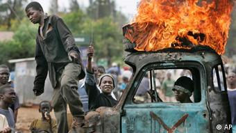 A Kenyan man sits in the cab of a destroyed truck used as a makeshift roadblock while a tyre burns on the roof, as he and others enforce the roadblock in Kisumu, Kenya, Tuesday, Jan. 29, 2008. The town of Kisumu is now almost completely ethnically cleansed of Kikuyus, and mobs armed with makeshift weapons erect burning roadblocks and search for the few Kikuyu targets remaining. (AP Photo/Ben Curtis)***Zu Dohrenbusch, Keine Entspannung der Lage in Sicht - Kenianischer Oppositionspolitiker in Nairobi erschossen***