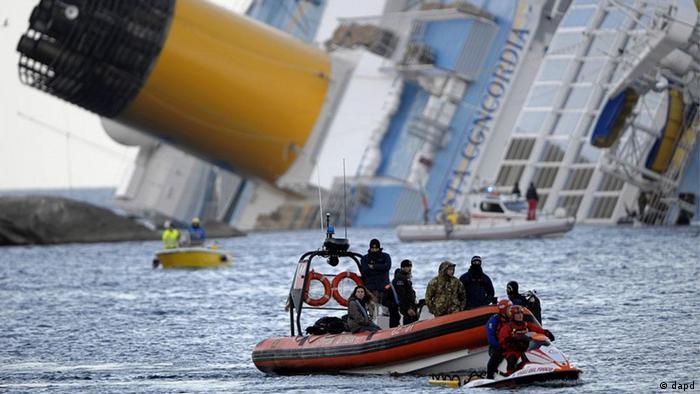 Taucher mit Schlauchbooten vor dem schräg im Wasser liegenden Schiff