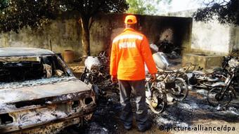 A rescue worker inspects the burnt-out wreckage of cars and motorcycles destroyed by multiple explosions