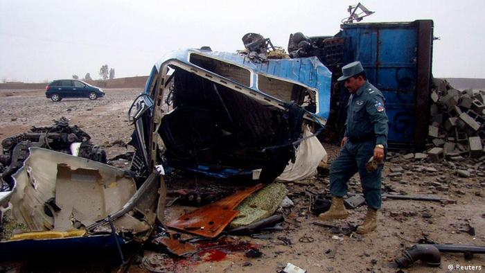An Afghan policeman inspects the wreckage of civilian car hit by a roadside bomb in Helmand province January 21, 2012. A roadside mine killed four civilians and wounded two in Lashkar Gah city, Helmand province, on Saturday, said Kamaluddin Shirzai, a senior police detective in the southern province. REUTERS/Abdul Malik (AFGHANISTAN - Tags: CIVIL UNREST CRIME LAW)
