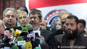 Muslim Brotherhood's Freedom and Justice Party President Mohammed Morsy (C) speaks as Emad Abdel Ghafour, chairman of the Salafi Nour Party (R) and businessman Ramy Lakeh (L) look on during a press conference in Cairo +++(c) dpa - Bildfunk+++