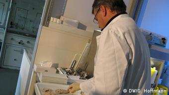 A scientist looks into a microscope Photo: Grit Hoffmann/DW