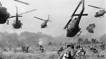 In this March 1965 file photo, hovering US Army helicopters pour machine gun fire into a tree line to cover the advance of South Vietnamese ground troops