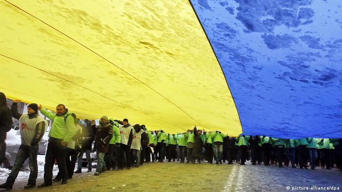 Люди несут огромный флаг Украины