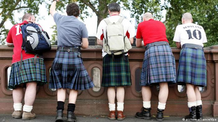 Five soccer fans from Scotland with their traditional kilt outfit stand on a bridge over Frankfurt's main river watching tevee broadcast of the England vs Trinidad and Tobago World Cup soccer match Thursday evening, June 15, 2006. Match was one by the English team 2-0. DPA/Frank Rumpenhorst dpa/lhe +++(c) dpa - Bildfunk+++