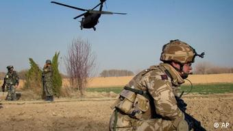A British soldier with the NATO led-International Security Assistance Force (ISAF) takes position as an helicopter belonging to ISAF flies over in Nad Ali district, Helmand province, south of Kabul, Afghanistan, on Monday, Feb. 15, 2010. (ddp images/AP Photo/Abdul Khaleq)
