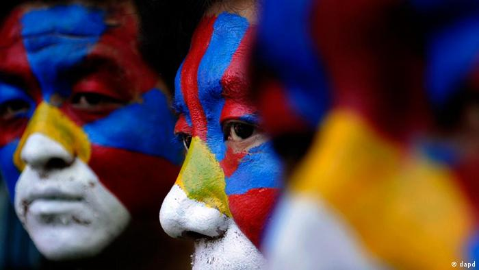 Tibetan exiles with faces painted in the Tibetan flag colors